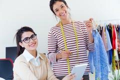 Två unga affärskvinnor som arbetar med den digitala minnestavlan i henne som är offic Arkivfoton
