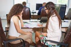 Två unga affärskvinnor som gör ett schema Royaltyfri Foto