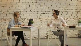 Två unga affärskvinnor som har ett möte i kontorssammanträdet stock video