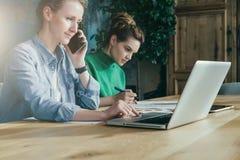 Två unga affärskvinnor som i regeringsställning sitter på tabellen och arbete tillsammans På tabellbärbar dator- och pappersdiagr fotografering för bildbyråer