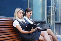 Två unga affärskvinnor som sitter på en bänk Arkivbilder