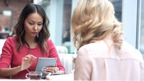 Två unga affärskvinnor som sitter på tabellen i kafé, genom att använda den digitala minnestavlan Royaltyfri Foto