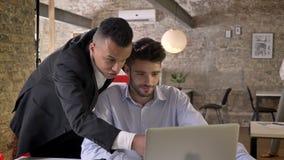 Två unga affärsmän håller ögonen på på bärbara datorn i regeringsställning och att knyta kontakt med teknologier, det funktionsdu arkivfilmer