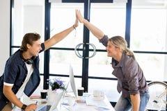 Två unga affärsmän i regeringsställning som firar framgång arkivfoton