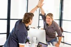 Två unga affärsmän i regeringsställning som firar framgång royaltyfria foton