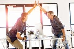 Två unga affärsmän i regeringsställning som firar framgång royaltyfri foto