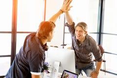 Två unga affärsmän i regeringsställning som firar framgång royaltyfri bild