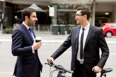 Två unga affärsmän med en cykel i stadsmitt Royaltyfria Bilder