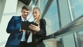 Två unga affärsmän meddelar om affär i kontoret Mot bakgrunden av ett stort ljust fönster arkivfilmer