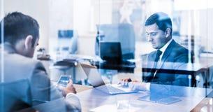 Två unga affärsmän som använder bärbar datordatoren på affärsmötet Fotografering för Bildbyråer