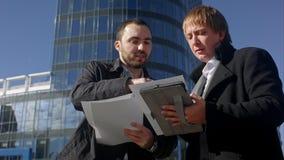 Två unga affärsmän som diskuterar dokumentet royaltyfri fotografi