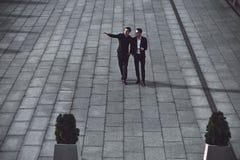 Två unga affärsmän som går i gatan royaltyfri fotografi