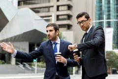 Två unga affärsmän som haglar för en taxi Arkivfoton