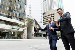 Två unga affärsmän som haglar för en taxi Arkivbild