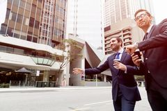 Två unga affärsmän som haglar för en taxi royaltyfria bilder