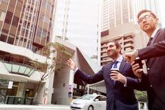 Två unga affärsmän som haglar för en taxi Royaltyfri Bild