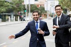 Två unga affärsmän som haglar för en taxi Royaltyfria Foton