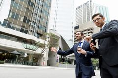 Två unga affärsmän som haglar för en taxi Fotografering för Bildbyråer