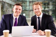 Två unga affärsmän som har kaffe, genom att använda en bärbar datordator Royaltyfri Fotografi