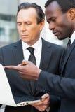 Två unga affärsmän som talar om affär, medan ett av dem benägenheten på datoren övervakar royaltyfri bild
