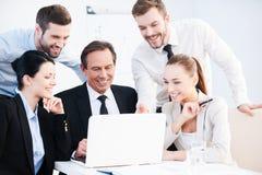 Två unga affärsmän som talar om affär, medan ett av dem benägenheten på datoren övervakar Arkivfoto