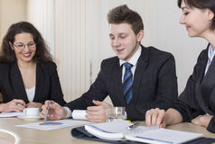 Två unga affärsmän som talar om affär, medan ett av dem benägenheten på datoren övervakar Arkivbild