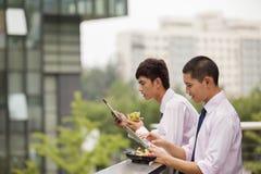 Två unga affärsmän som utomhus arbetar och äter över lunchavbrott Arkivbild