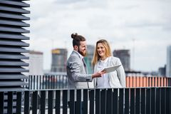 Två unga affärspersoner med minnestavlaanseende på en terrass utanför kontoret som arbetar royaltyfri foto