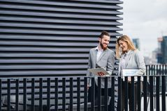 Två unga affärspersoner med minnestavlaanseende på en terrass utanför kontoret som arbetar royaltyfria foton