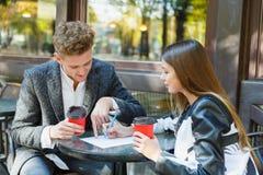 Två unga affärspersoner som använder den digitala minnestavlan på ett möte på coffee shop arkivbilder