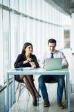 Två unga affärspersoner som sitter på tabellen med bärbar datordatoren inom kontoret royaltyfria bilder