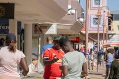 Två unga afrikanska män i konversation på afrikanska stadsgatawi Arkivbild