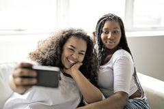 Två unga afro flickor som har gyckel tillsammans fotografering för bildbyråer