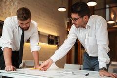 Två unga allvarliga affärsmän som arbetar på ett affärsplan arkivfoto