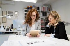 Två unga arkitekter som tillsammans i regeringsställning arbetar Fotografering för Bildbyråer