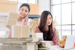 Två unga asiatiska affärsmän i den tillfälliga klänningen som är upptagen med att få eller arkivfoto