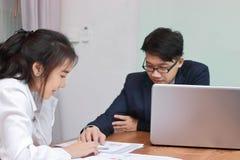 Två unga asiatiska affärspersoner som tillsammans analyserar skrivbordsarbete eller diagram i modernt kontor Lagarbetsaffärsidé S royaltyfri bild