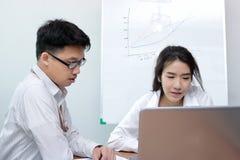 Två unga asiatiska affärspersoner som tillsammans arbetar på en bärbar datordator på kontoret arkivfoto