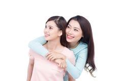 Två unga asiatiska flickvänner i hoodies som har gyckel tillsammans whit Fotografering för Bildbyråer