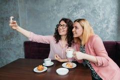 Två unga attraktiva kvinnavänner tar selfie fotografering för bildbyråer