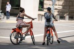 Två unga attraktiva kvinnlig på cyklar royaltyfri foto