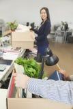Två unga bärande askar för affärsfolk med kontorsobjekt arkivbild