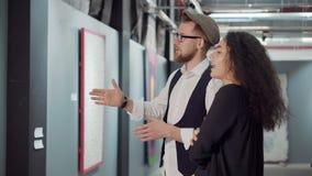 Två unga besökare av konstutställningen diskuterar en bild i en korridor lager videofilmer