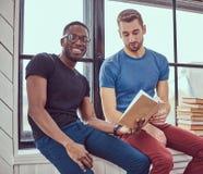 Två unga blandras- studenter som arbetar med böcker som sitter på en w Royaltyfri Foto