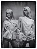 två unga blonda kvinnliga skyltdockor som bär vit skjortor och jeans royaltyfria foton