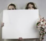 Två unga brudar som rymmer det tomma tecknet Royaltyfria Bilder