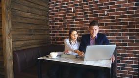 Två unga Businesspeople som arbetar på bärbara datorn i coffee shop lager videofilmer