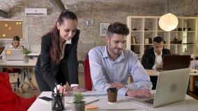 Två unga businesspeople talar, hålla ögonen pådiagram och bärbara datorn i regeringsställning och att knyta kontakt med teknologi stock video