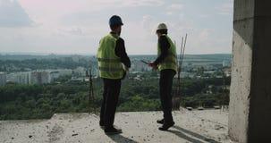 Två unga byggnadsarbetare som ser till och med byggnaden och, har en diskussion stock video