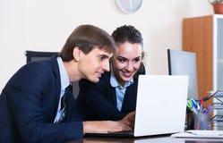Två unga chefer som använder bärbara datorn på arbete Arkivbild